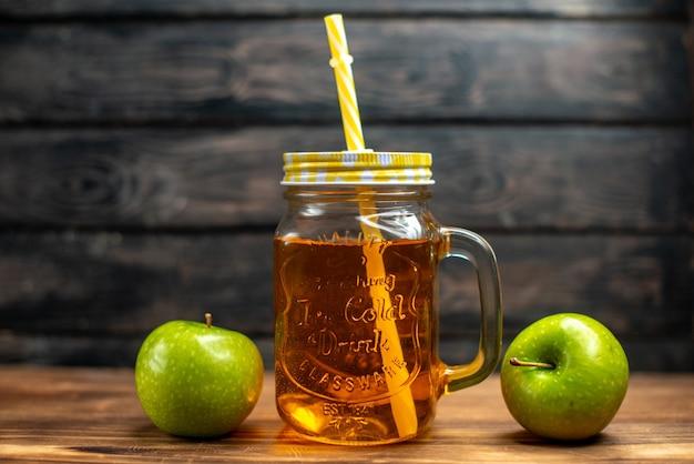 Vista frontale del succo di mela fresco all'interno della lattina con paglia su colori scuri della foto della bevanda alla frutta del cocktail