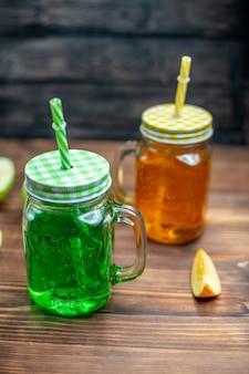 暗い果物の缶の中の新鮮なリンゴ ジュースの正面図ドリンク カクテル バーの色