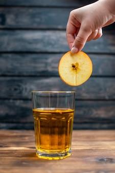 Vista frontale succo di mela fresco all'interno del bicchiere su bevanda scura foto cocktail bar colore frutta