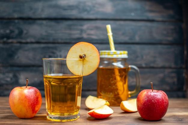 茶色の木製の机の写真のカクテル フルーツ ドリンクの色に新鮮なリンゴと新鮮なリンゴ ジュースの正面図
