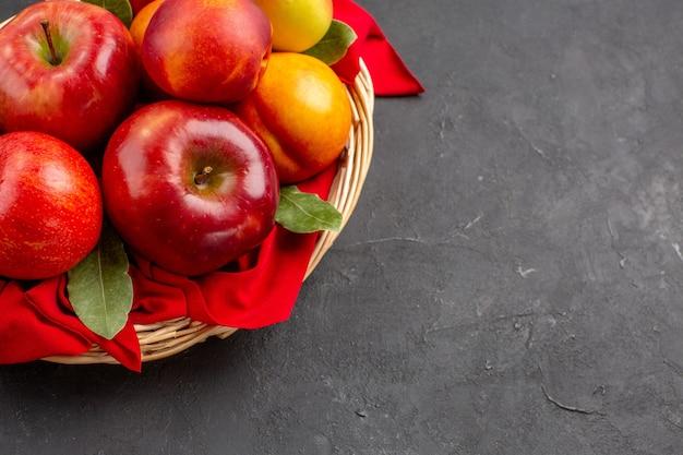Vista frontale mele fresche all'interno del cesto sul tavolo scuro frutta fresca matura