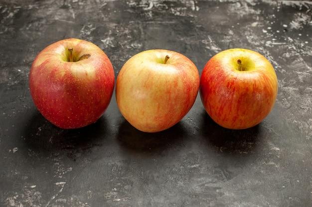 Vista frontale mele fresche allineate su foto scura frutta matura vitamina albero colore morbido succo