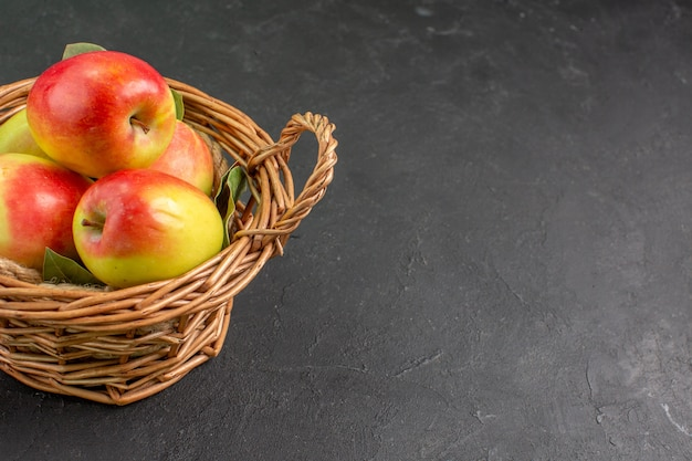 Vista frontale mele fresche frutti maturi all'interno del cesto sulla scrivania grigia frutta fresca matura