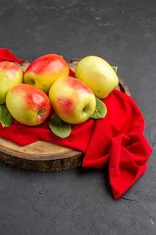 Вид спереди свежие яблоки, спелые фрукты на красной ткани и серый стол, спелые свежие фруктовые деревья