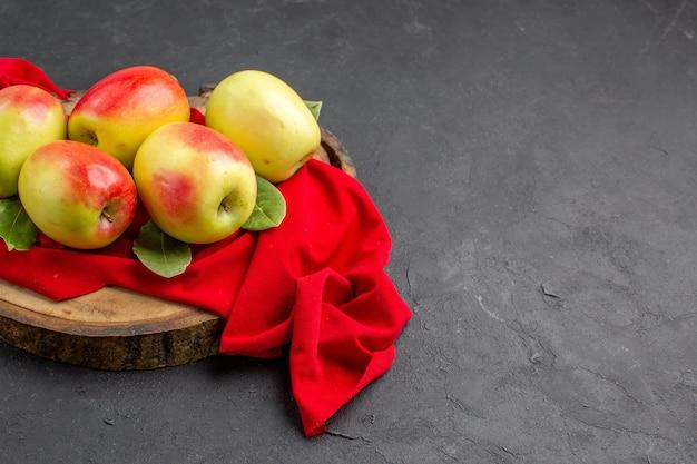 Vista frontale mele fresche frutti maturi su tessuto rosso e pavimento grigio albero da frutto fresco maturo