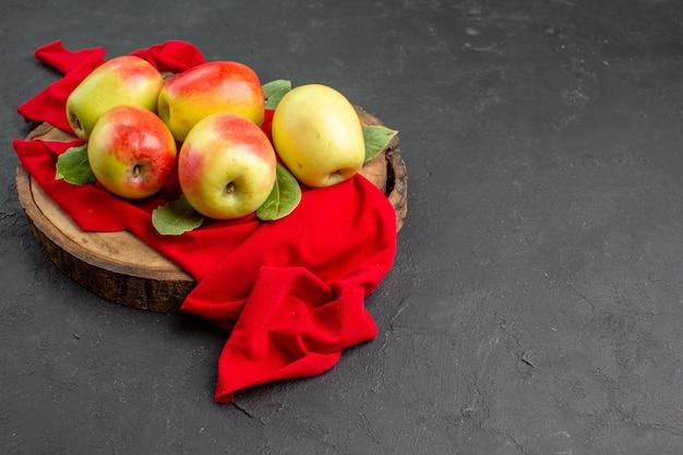 Vista frontale mele fresche frutti maturi su tessuto rosso e tavolo grigio frutti freschi maturi