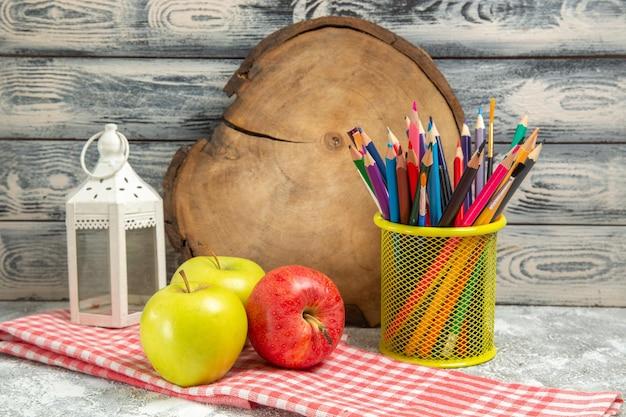 Вид спереди свежие яблоки с красочными карандашами на сером фоне спелых спелых свежих фруктов