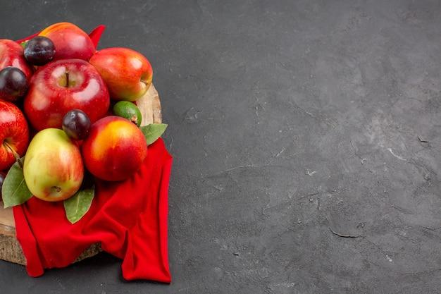 어두운 탁자에 잘 익은 부드러운 주스 나무에 복숭아와 자두가 있는 신선한 사과