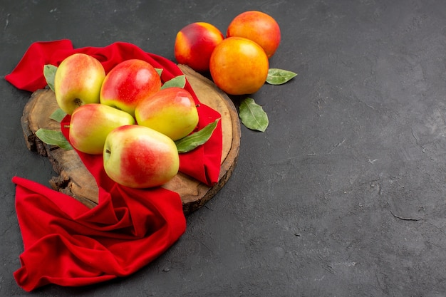 Vista frontale mele fresche con pesche sull'albero da frutto maturo fresco di colore scuro della tavola