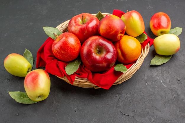Vista frontale mele fresche con pesche sul tavolo scuro succo maturo di alberi da frutto