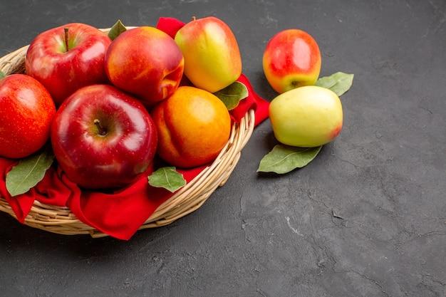 Vista frontale mele fresche con pesche sul tavolo scuro frutta matura succo dolce