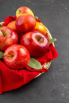 Vista frontale mele fresche con pesche all'interno del cesto sul tavolo scuro albero da frutto fresco maturo