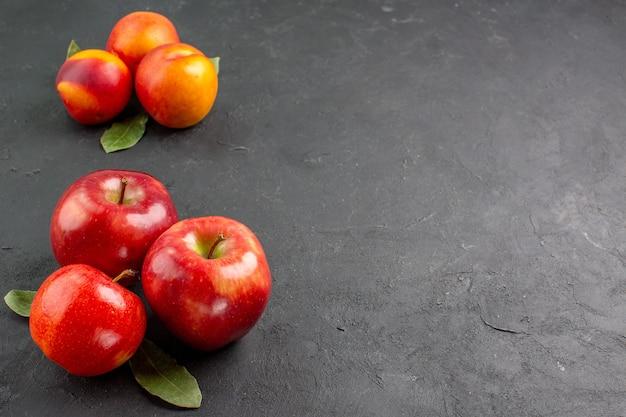 어두운 탁자에 복숭아가 있는 신선한 사과 전면 보기 신선한 익은 과일