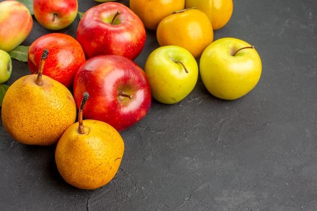Вид спереди свежие яблоки с грушами и хурмой на темном столе, свежее спелое спелое дерево