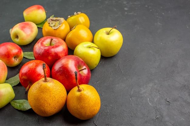 Vista frontale mele fresche con pere e cachi sul pavimento scuro fresco maturo morbido