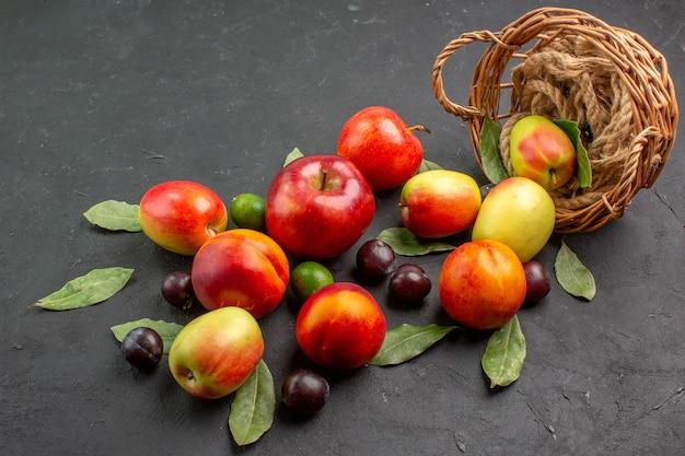 暗いテーブルの熟したジュースのまろやかな上にプラムと桃の正面図新鮮なリンゴ