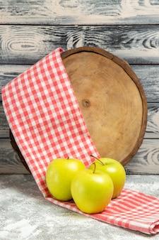 Vista frontale mele fresche con asciugamano su sfondo grigio frutta fresca matura pianta dolce albero