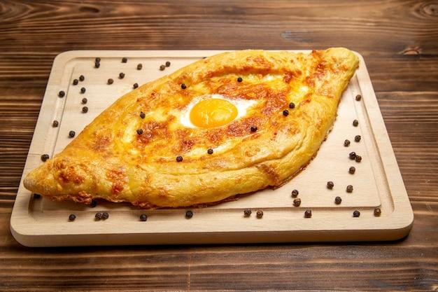 Pane appena sfornato di vista frontale con l'uovo cotto sul pasto del panino delle uova della colazione dell'alimento della pasta dello scrittorio marrone