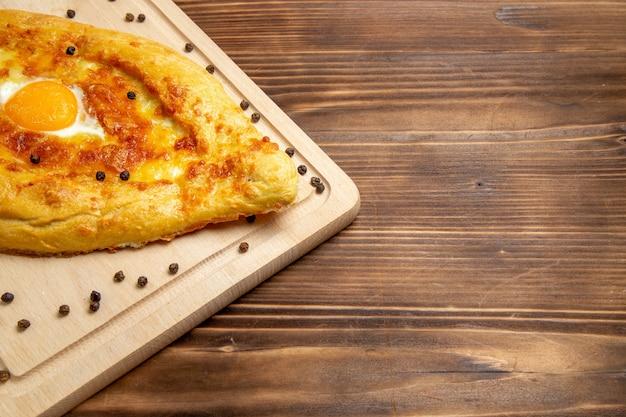 Vista frontale pane appena sfornato con uovo cotto sulla superficie rustica marrone cibo pasta colazione cuocere panino pasto