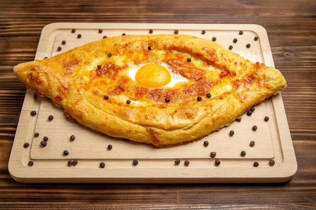 Pane appena sfornato di vista frontale con l'uovo cotto sul pasto del panino dell'uovo della prima colazione dell'alimento della pasta di superficie rustica marrone