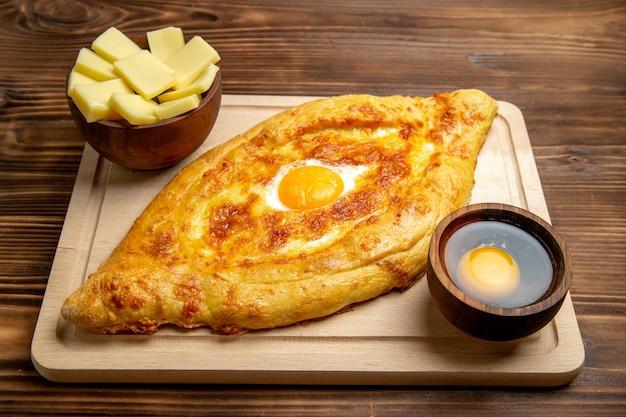 Pane appena sfornato di vista frontale con l'uovo cotto sul cibo a base di uova della colazione del panino del pasto della pasta dello scrittorio di legno marrone