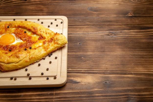 正面図茶色の素朴な机の上の調理された卵と焼きたてのパン生地食品朝食卵パン食事