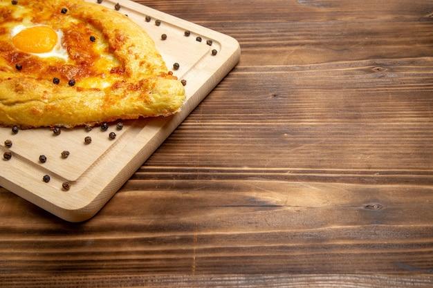 Вид спереди свежеиспеченный хлеб с вареным яйцом на деревенской поверхности тесто еда завтрак яичная булочка