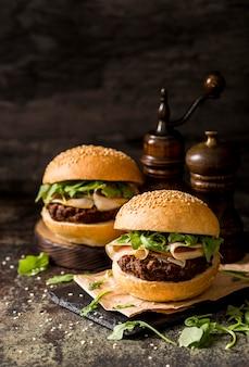 Свежие гамбургеры из говядины с беконом на грифельной доске, вид спереди