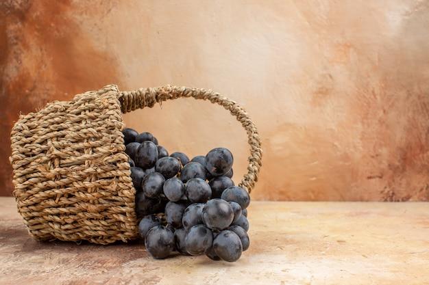 明るい背景のバスケットの中の新鮮な黒ブドウの正面図フルーツワインまろやかな熟した写真