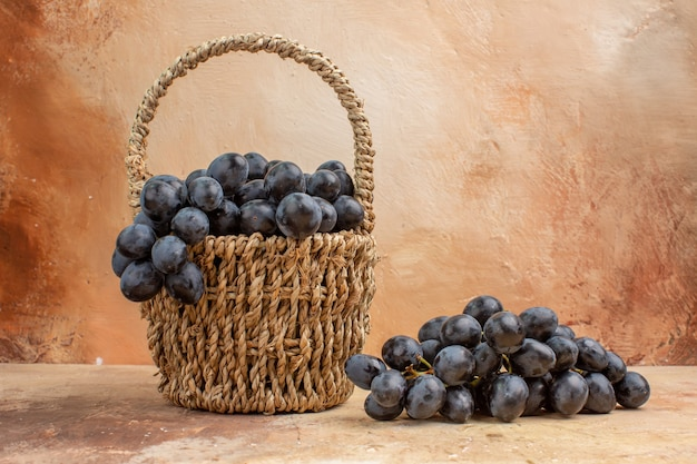 明るい背景のフルーツワインの色の写真のバスケット内の新鮮な黒ブドウの正面図