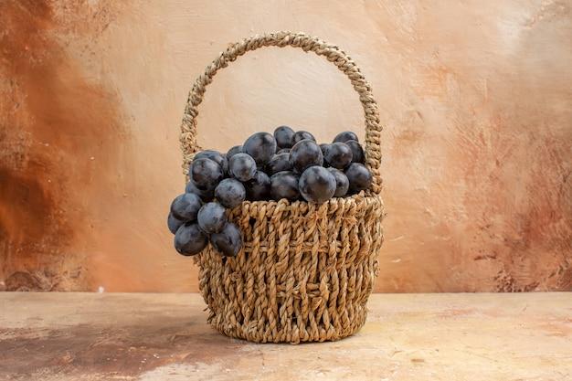 明るい背景のフルーツワインのカラー写真のバスケット内の新鮮な黒ブドウの正面図