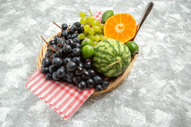 Вид спереди свежий черный виноград с апельсином и фейхоа на белом фоне спелые спелые свежие фрукты