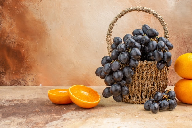 Vista frontale uva nera fresca con arancia su uno sfondo chiaro albero fotografico dolce vitamina frutta matura