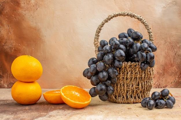 Vista frontale uva nera fresca con arancia su sfondo chiaro foto colore succo frutta dolce