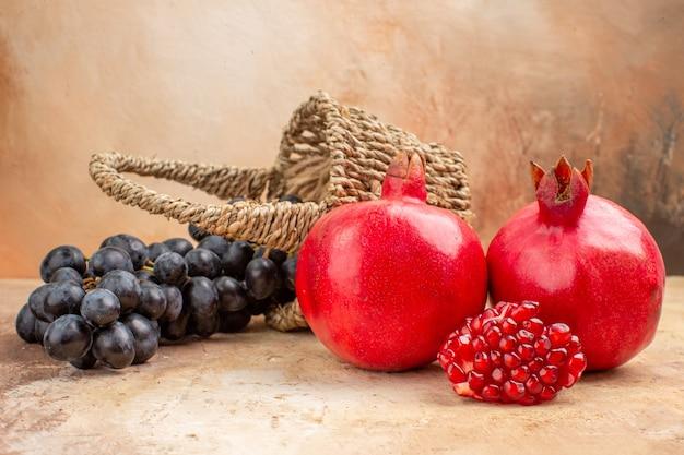 Vista frontale uva nera fresca con melograni su sfondo chiaro albero foto dolce vitamina frutta matura