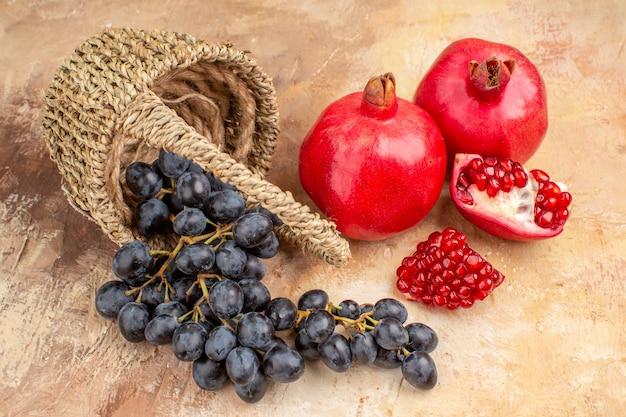 Vista frontale uva nera fresca con melograni sullo sfondo chiaro frutta matura dolce albero foto vitamina