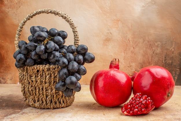 正面図明るい背景にザクロと新鮮な黒ブドウ熟したフルーツワインまろやかな写真