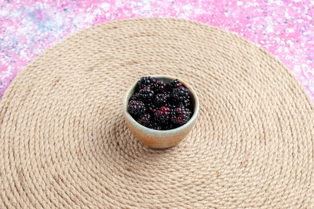 Свежая ежевика вида спереди внутри маленького горшка на розовом столе.