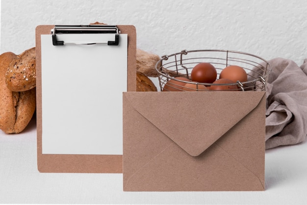 Front view fresh bread and eggs with envelope and blank clipboard
