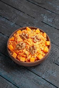 Vista frontale insalata di carote fresche grattugiate con noci e aglio sulla scrivania scura dieta insalata di noci colore salute