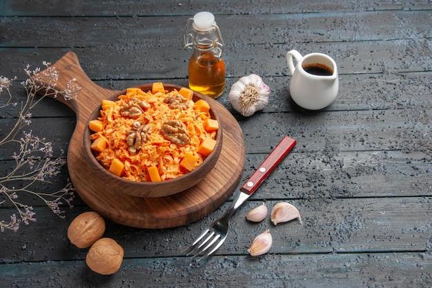 正面図新鮮なニンジンサラダすりおろしたサラダとクルミのダークデスクダイエットカラーナッツ健康サラダ