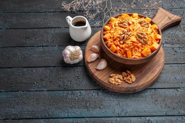 ダークブルーのデスクナッツダイエット健康サラダの色にニンニクとクルミの正面図新鮮なニンジンサラダ