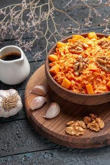 Vista frontale insalata di carote fresche con aglio e noci su colore blu scuro dell'insalata di salute della dieta del dado della scrivania