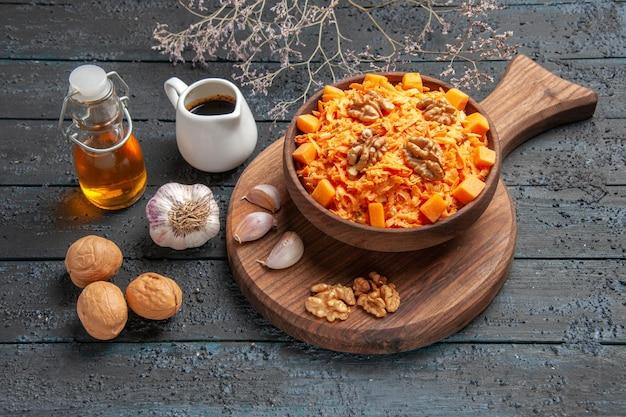 Insalata di carote fresca vista frontale con aglio e noci sulla salute del colore dell'insalata di dieta del dado della scrivania blu scuro
