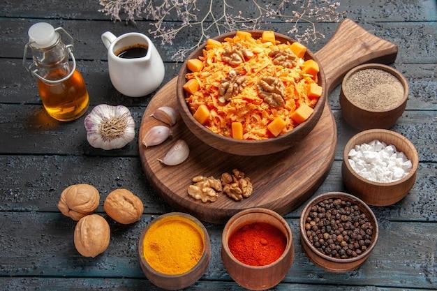 Insalata di carote fresca di vista frontale con noci e condimenti sulla salute dell'insalata di dieta di noci di colore blu scuro della scrivania