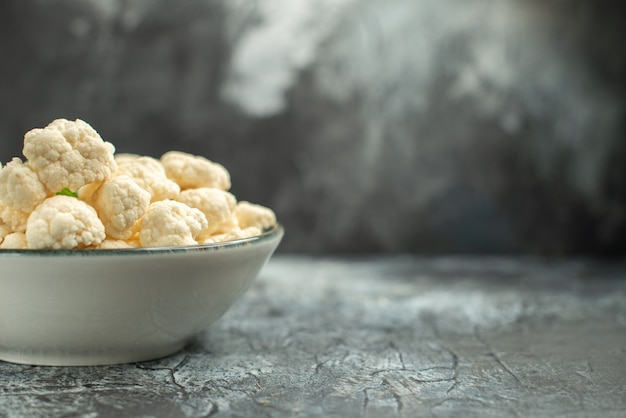 Vista frontale cavolfiore fresco all'interno del piatto sulla superficie grigio chiaro
