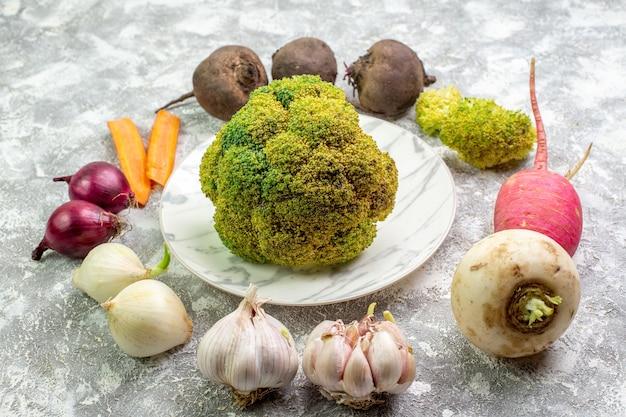 Cavolfiore fresco di vista frontale con aglio e cipolle del ravanello della barbabietola su superficie bianca