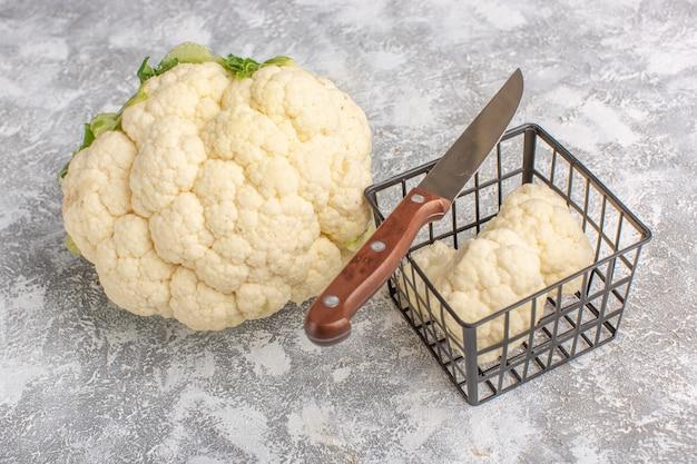 Vista frontale del cavolfiore fresco con il coltello sul colore crudo del pasto di cibo vegetale leggero backgruond