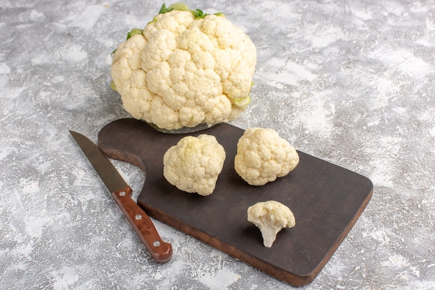 Front view of fresh cauliflower with knife and on the light-white wall