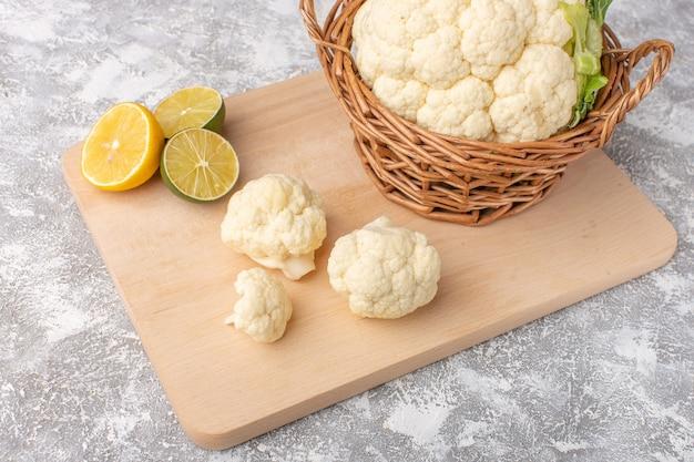 Vista frontale del cavolfiore fresco con il limone sul colore grezzo del pasto di cibo vegetale backgruond bianco-chiaro